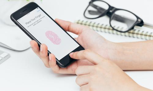 Woman using fingerprint scanner on an iPhone